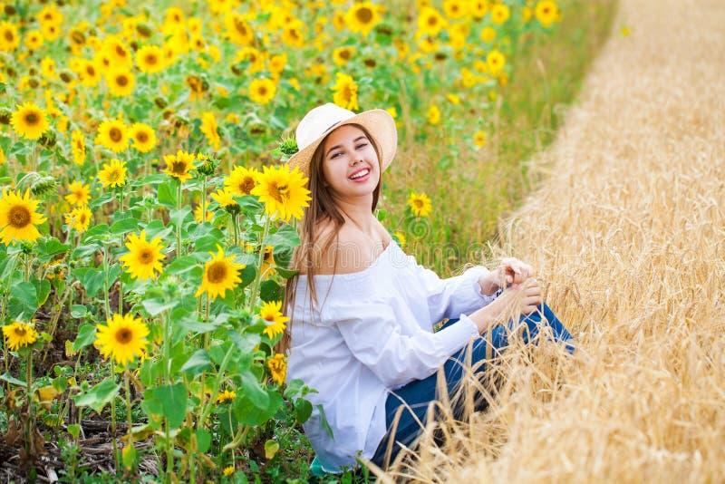 白色女衬衫的深色的妇女坐金黄麦子和向日葵领域背景  免版税库存图片