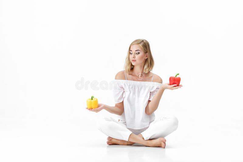 白色女衬衫的美丽的白肤金发的妇女选择黄色或红色甜椒 饮食健康 免版税库存图片