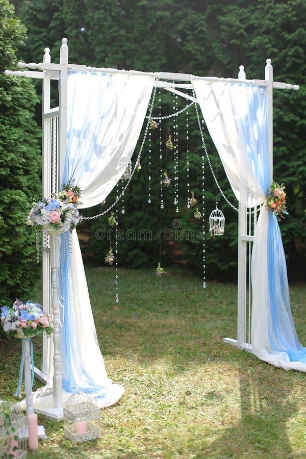 白色婚礼曲拱在庭院里 图库摄影