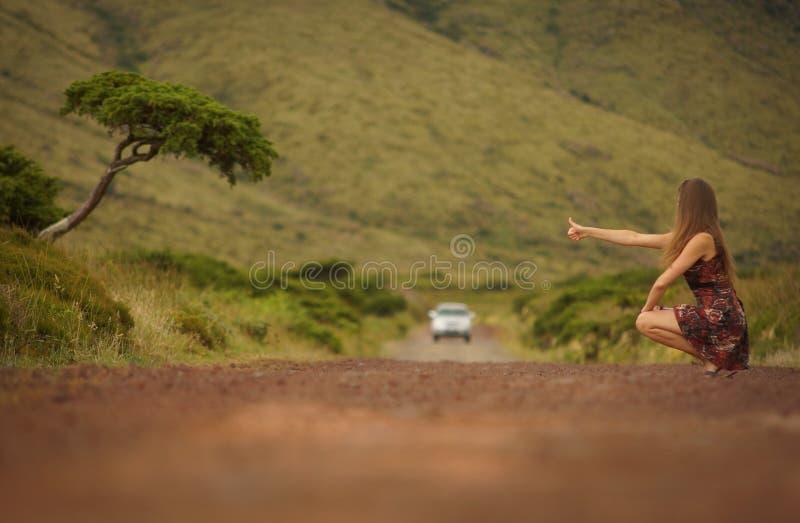 白色婚礼礼服的年轻新娘在弗洛勒斯海岛美丽的景色背景,搭在路的AzoresYoung妇女便车我 免版税库存照片