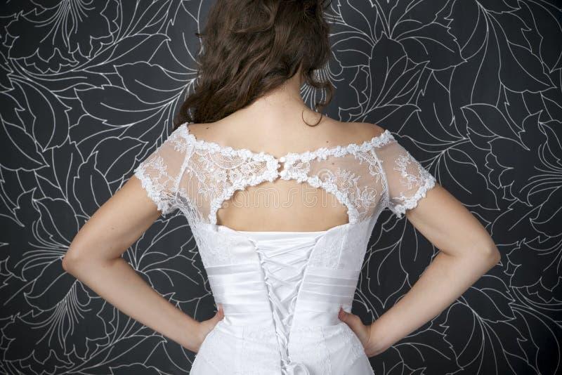 白色婚礼礼服的美丽的妇女与束腰 库存照片