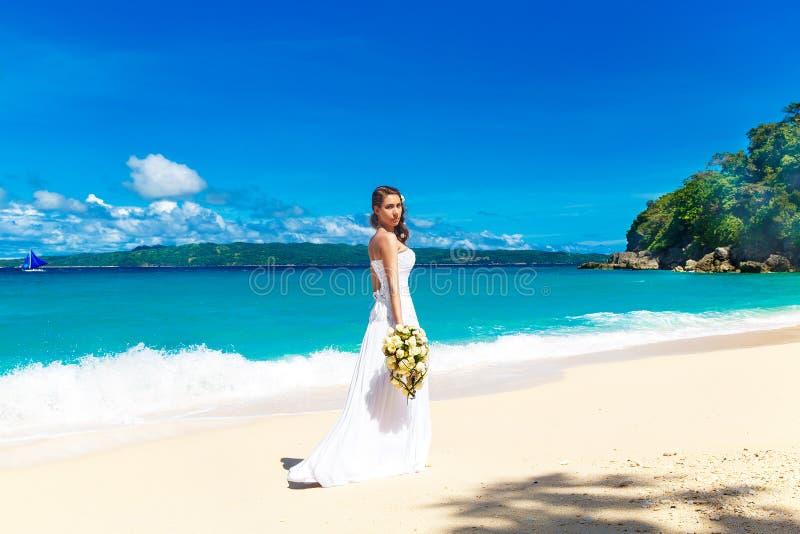 白色婚礼礼服的美丽的深色的新娘与大长的wh 免版税图库摄影