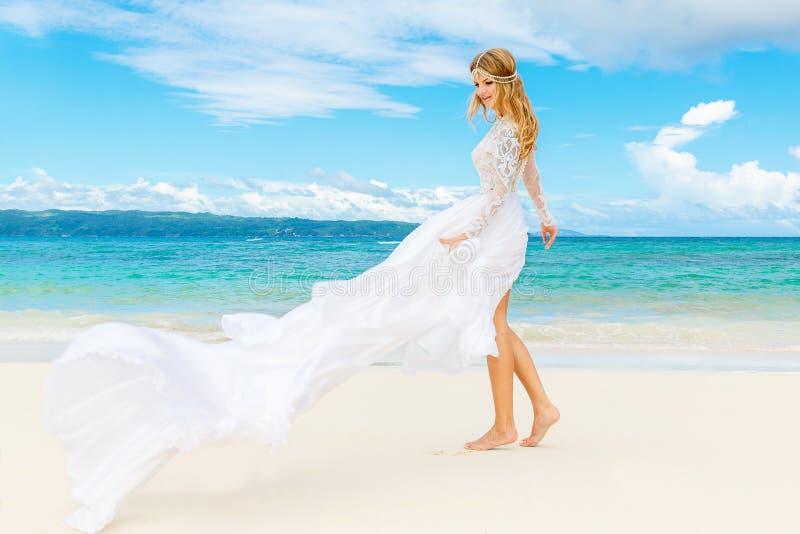 白色婚礼礼服的美丽的白肤金发的新娘与大长的火车 库存照片
