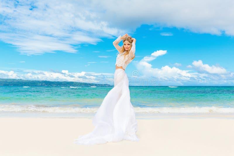 白色婚礼礼服的美丽的白肤金发的新娘与大长的火车 免版税库存图片
