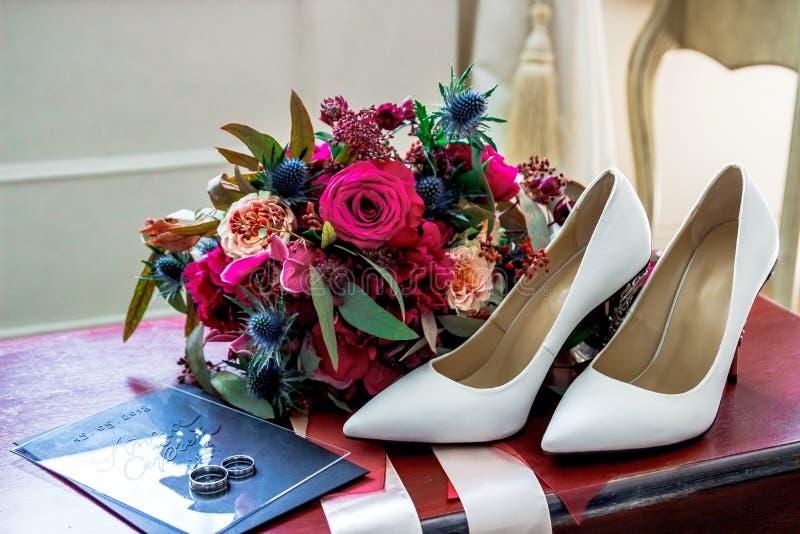 白色婚礼穿上鞋子新娘、婚戒和花束 免版税库存照片