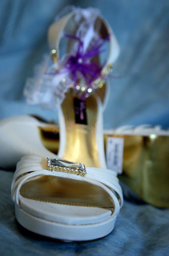 白色婚礼鞋子和袜带在蓝色背景 免版税库存图片