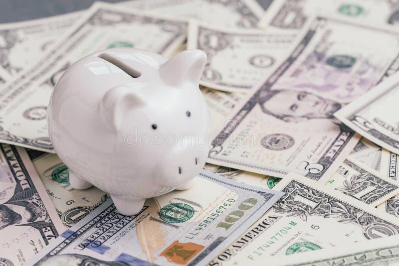 白色存钱罐或硬币银行堆的美元钞票金钱、投资成长、财政背景或者挽救储蓄 库存图片