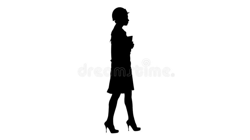 白色实验室外套和白色安全安全帽的走剪影可爱的西班牙的妇女拿着笔记本或片剂 库存照片