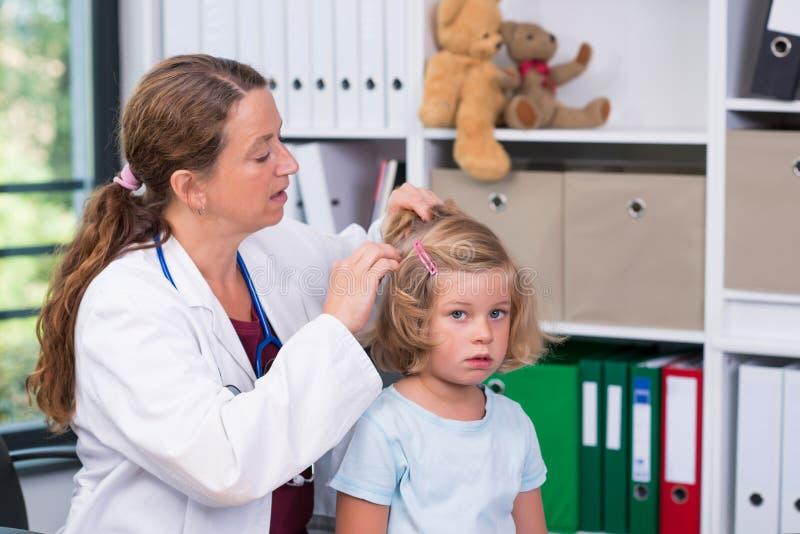 白色实验室外套的女性儿科医生审查了小患者fo 免版税库存照片