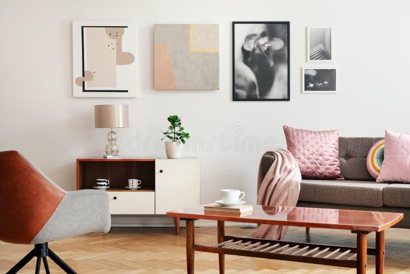 白色客厅内部真正的照片与海报的在墙壁、长沙发有坐垫的和毯子,木咖啡桌上与书和 库存照片