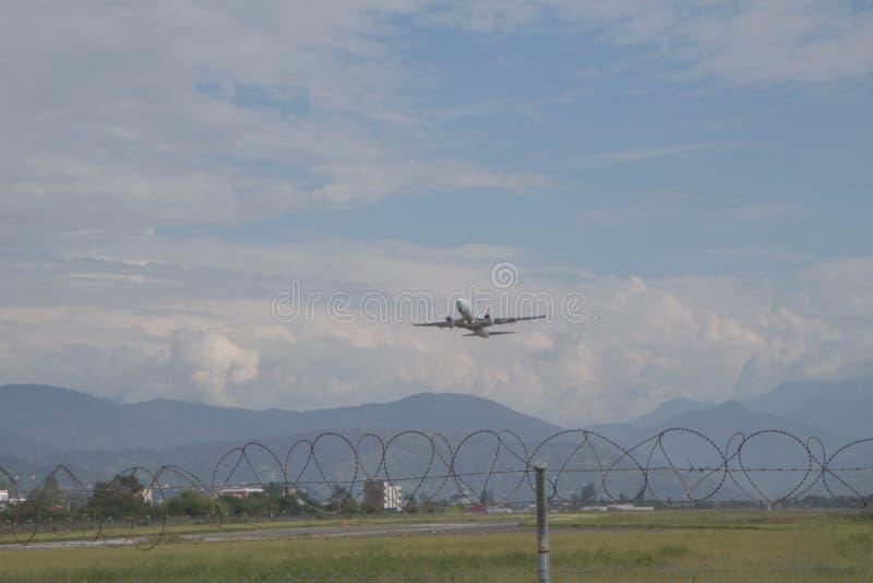 白色客机从机场飞行  免版税库存图片