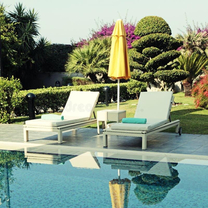 白色室外家具和黄色伞在手段游泳附近 库存图片