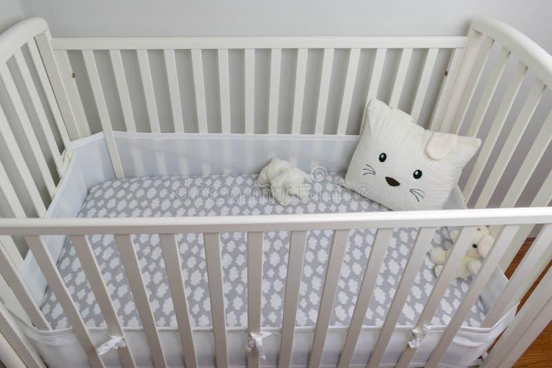 白色小儿床和浅灰色的墙壁婴孩` s室的 图库摄影