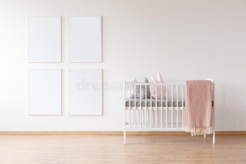 白色小儿床和海报大模型 库存照片