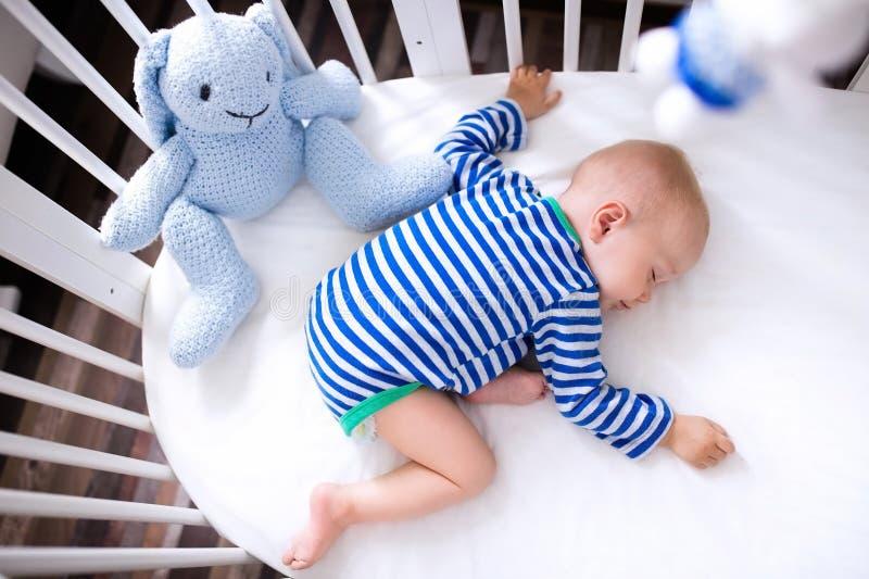 白色小儿床的睡觉的男婴 图库摄影