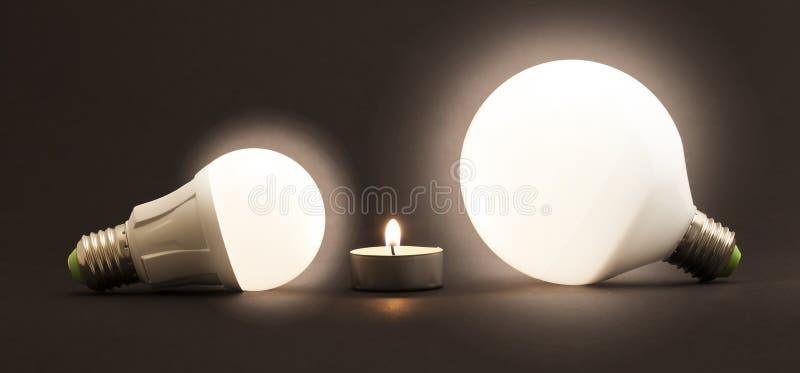 白色小的蜡烛和LED电电灯泡在黑暗的背景 C 免版税库存图片