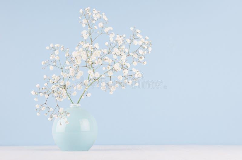 白色小蓬松花春天花束在蓝色光滑的圈子陶瓷花瓶的在软的白色木桌和淡色蓝色墙壁上 免版税库存照片