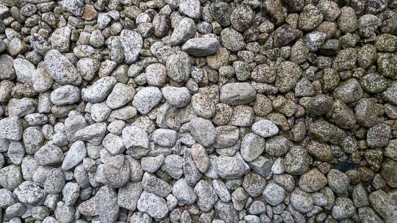 白色岩石在是在它旁边的日本石庭院样式是水的部分滴水下来和的地面被洒了 免版税库存图片