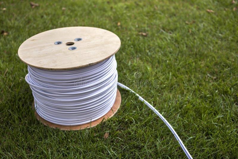 白色工业电缆卷顶视图在大木卷轴户外的绿草的 专业人员 免版税库存图片