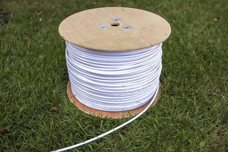 白色工业电缆卷顶视图在绿草隔绝的户外大木卷轴的 专业人员 免版税库存照片