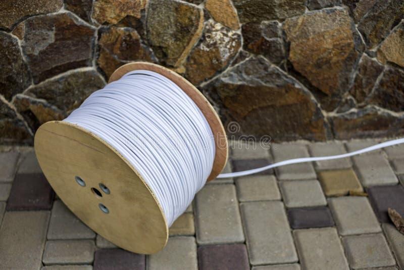 白色工业电缆大卷在大木卷轴户外的在石篱芭背景的晴朗的路面的 库存图片