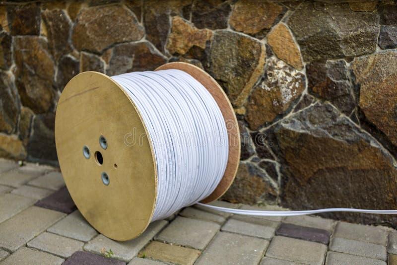 白色工业电缆大卷在大木卷轴户外的在石篱芭背景的晴朗的路面的 免版税库存图片