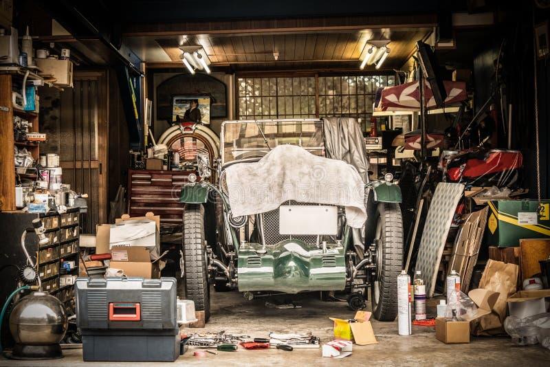 白色布料盖的减速火箭的葡萄酒汽车 在车库的整修项目与许多机械细节和工具 免版税库存照片