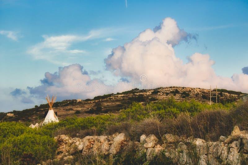 白色帆布圆锥形帐蓬在领域野营在一多云天空蔚蓝下 免版税库存照片