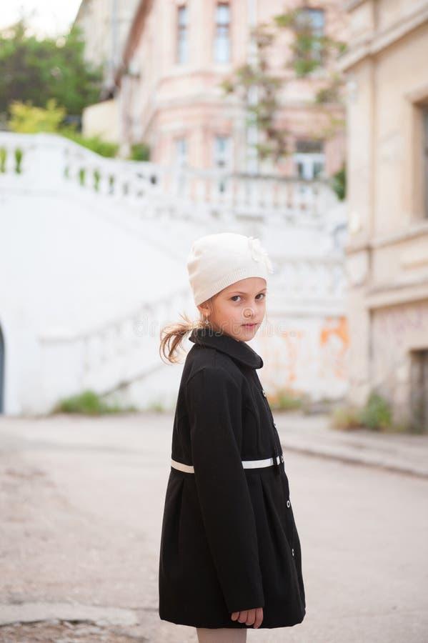 白色帽子和黑减速火箭的样式外套的俏丽的女孩在老镇街道上 免版税库存照片