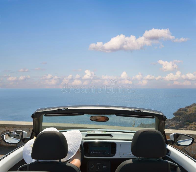 白色帽子的妇女在一辆开放汽车 免版税库存照片