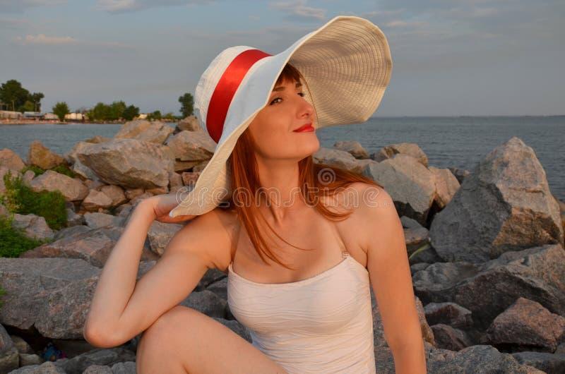 白色帽子的妇女有红色丝带的 库存图片