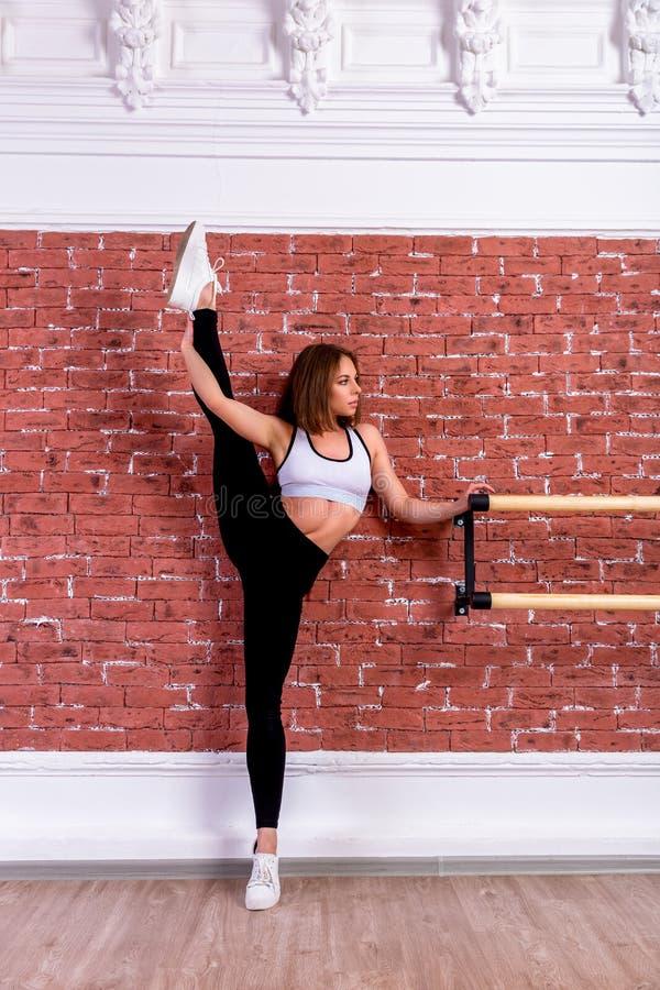 白色庄稼顶面和黑绑腿的年轻美丽的灵活的女孩在舞蹈演播室摆在 舒展和身体芭蕾题材 免版税库存图片