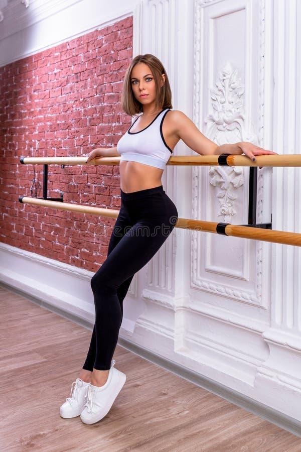 白色庄稼顶面和黑绑腿的年轻美丽的灵活的女孩在舞蹈演播室摆在 舒展和身体芭蕾题材 库存图片