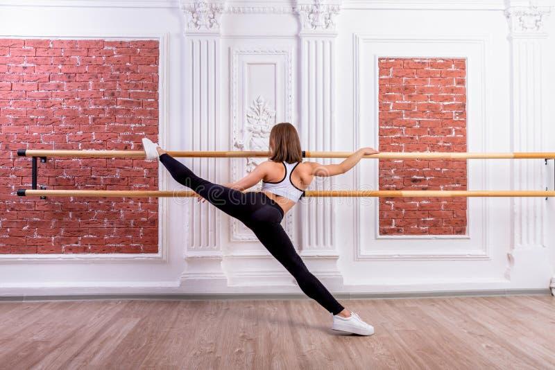 白色庄稼顶面和黑绑腿的年轻美丽的灵活的女孩在舞蹈演播室摆在 舒展和身体芭蕾题材 库存照片