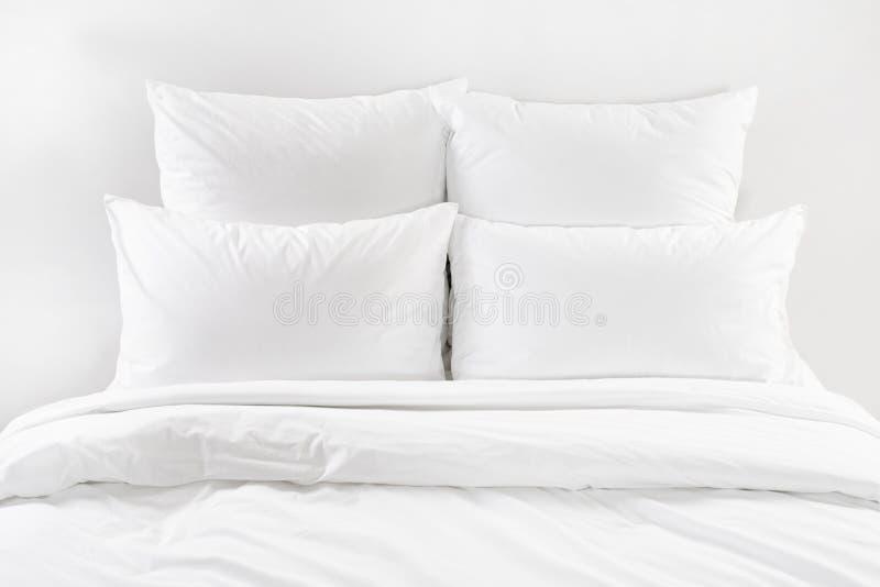 白色床、四个白色枕头和鸭绒垫子在床上 免版税库存图片