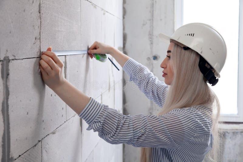 白色建筑盔甲的特写镜头白肤金发的女孩设计师工头由卷尺测量sibit灰色墙壁在房子里下 库存照片