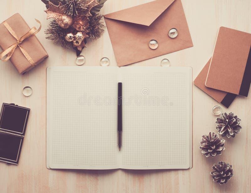 白色开放笔记薄、信封和说谎在米黄木背景,平展位置, copyspace的圣诞节装饰,定了调子图象 库存照片