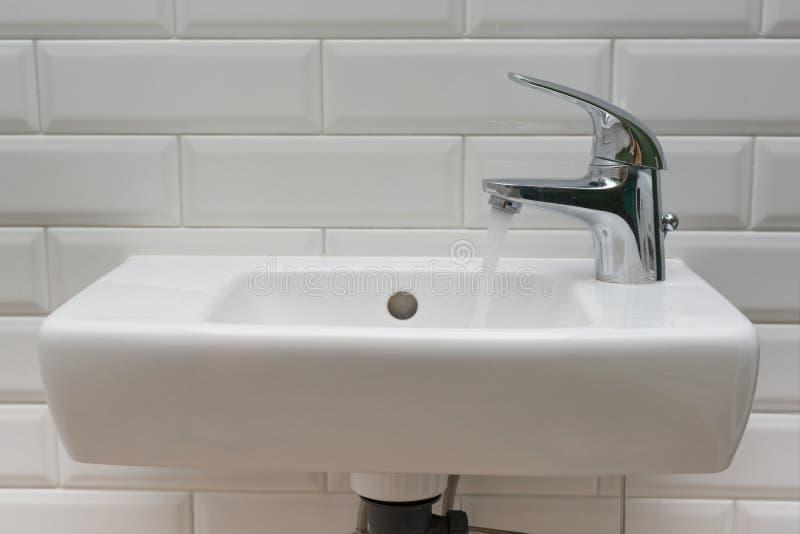 白色微型水盆特写镜头在洗手间的与开放镀铬物龙头水盆 免版税图库摄影