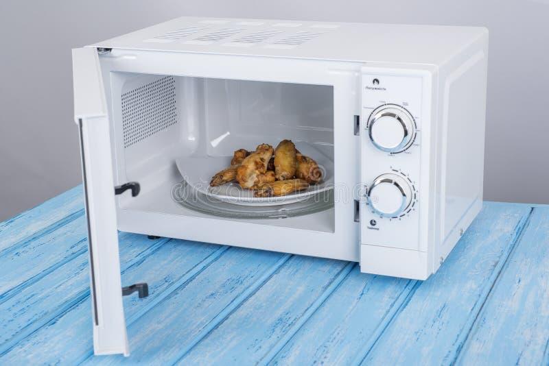白色微波炉,加热的食物的蓝色木表面上 免版税库存照片