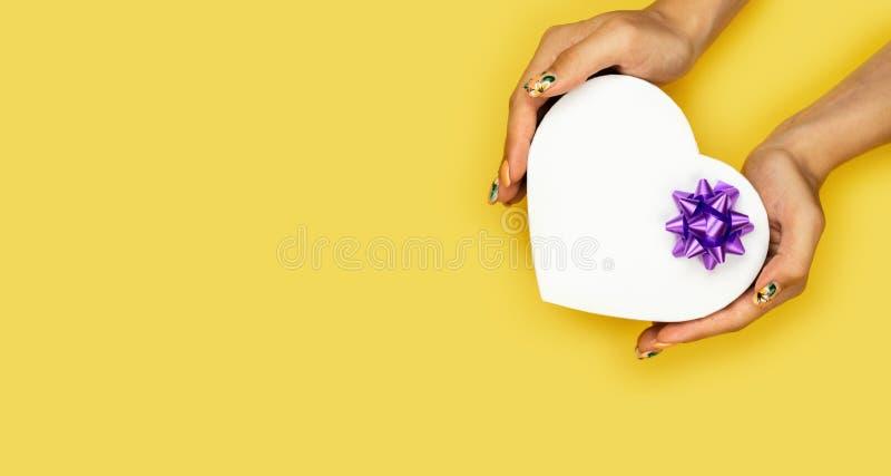 白色心形礼物盒在与拷贝空间的黄色背景隔绝的妇女手上 免版税库存图片