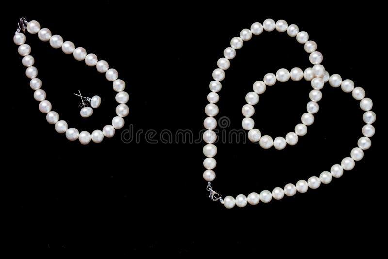 白色成珠状在黑背景和镯子隔绝的项链、耳环 免版税库存照片