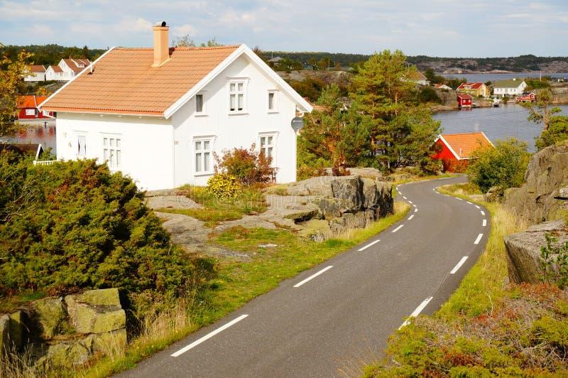 白色房子和路在海湾Kragero, Portor附近 免版税库存照片