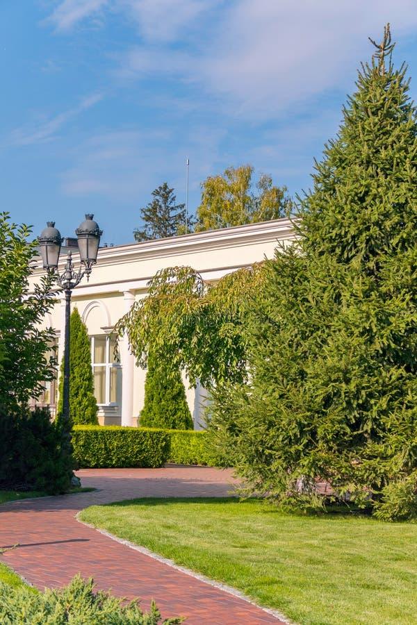 白色房子在有一个美好的风景设计的一个公园在清楚的蓝天下 Mezhyhirya乌克兰 库存图片