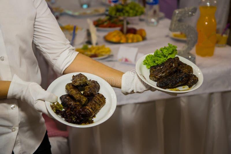 白色手套的女服务员拿着有肉盘的两块板材 餐馆承办酒席服务 免版税图库摄影
