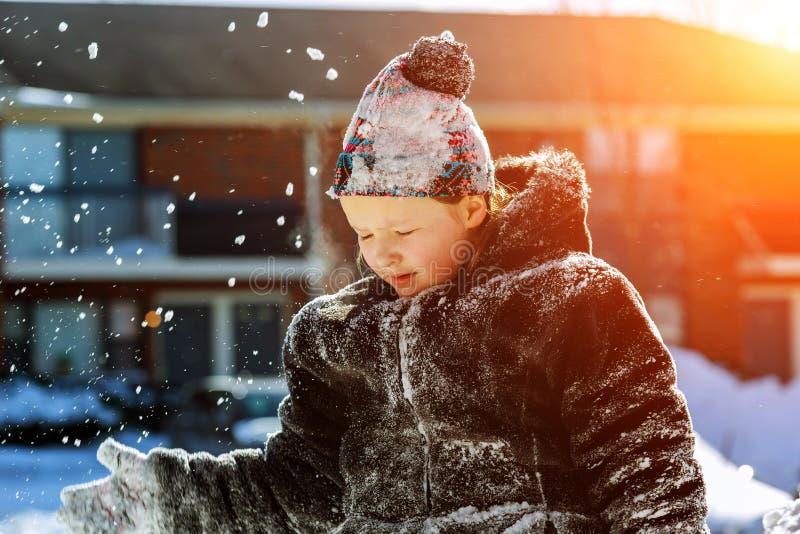 白色手套的愉快的小女孩走在冬天公园的投掷雪 免版税库存照片