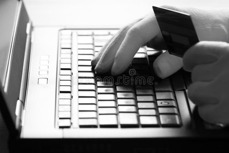 白色手套的计算机黑客窃取关于膝上型计算机的信息 库存图片