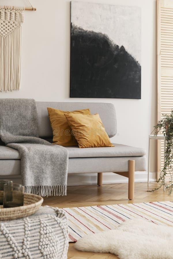 白色手工制造花边垂直的看法和在时髦客厅墙壁上的现代绘画内部与灰色时髦的长沙发与 库存图片