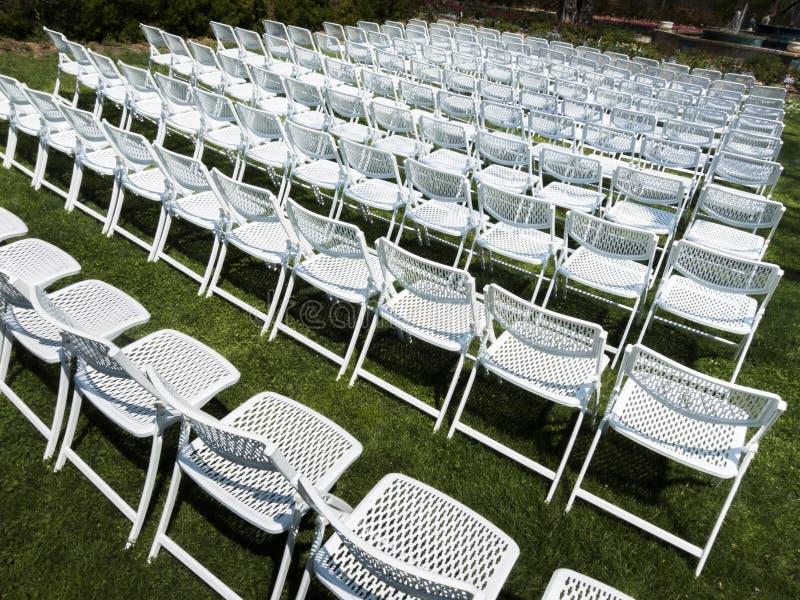 白色折叠椅的对称样式在室外庭院事件的 免版税库存图片
