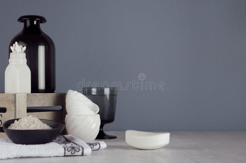 白色护肤品和辅助部件在白色木架子和深灰墙壁,典雅的卫生间装饰 免版税库存图片
