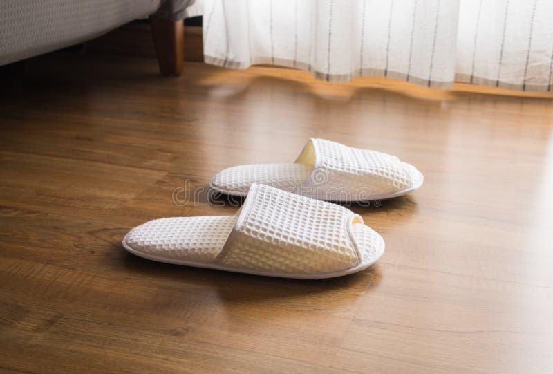白色拖鞋,在木地板上的鞋子在早晨 免版税库存图片